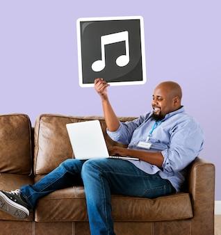 Mann, der einen laptop verwendet und eine musikalische anmerkung anhält