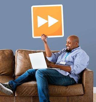 Mann, der einen laptop verwendet und einen schnellen vorwärtsknopf anhält