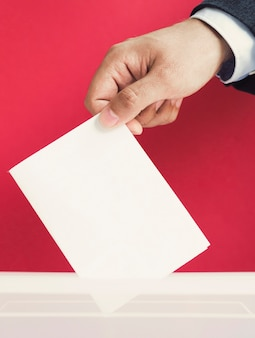 Mann, der einen leeren stimmzettel in ein kastenmodell einsetzt