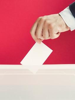 Mann, der einen leeren stimmzettel in einen kasten einsetzt