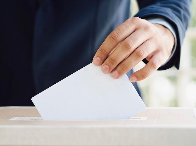 Mann, der einen leeren stimmzettel in wahlkasten einsetzt