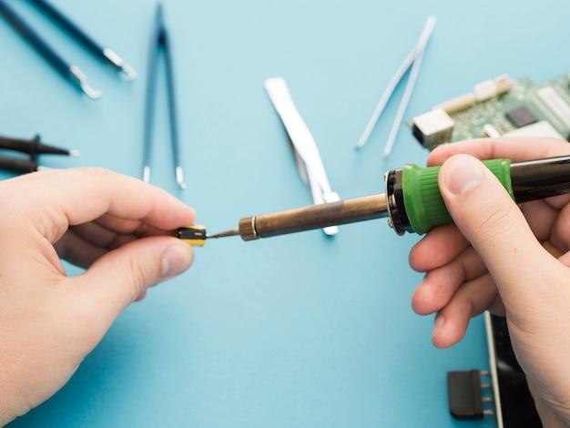 Mann, der einen lötkolben verwendet, um eine komponente zu reparieren