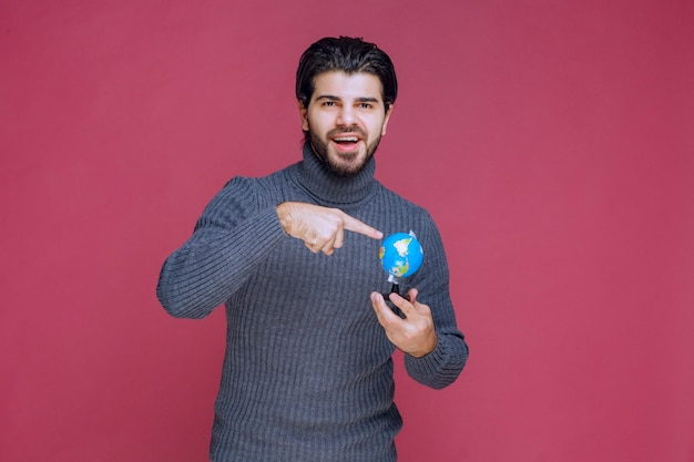 Mann, der einen mini-globus hält und eine präsentation darüber macht.