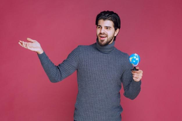 Mann, der einen mini-globus hält und grüße sendet.