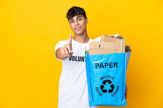 Mann, der einen recyclingbeutel voll papier hält, um auf isoliertem gelbem zeigen und anheben eines fingers zu recyceln