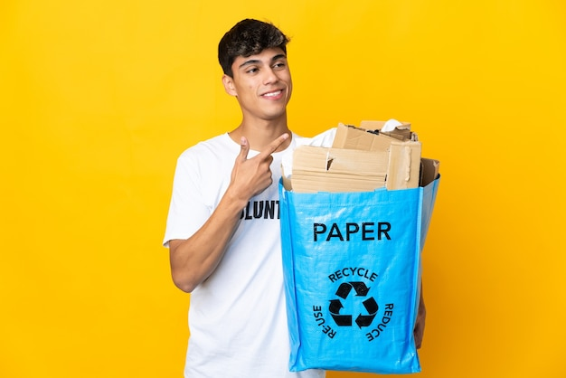 Mann, der einen recyclingbeutel voll papier hält, um über isolierte gelbe wand zu recyceln, die zur seite zeigt, um ein produkt zu präsentieren