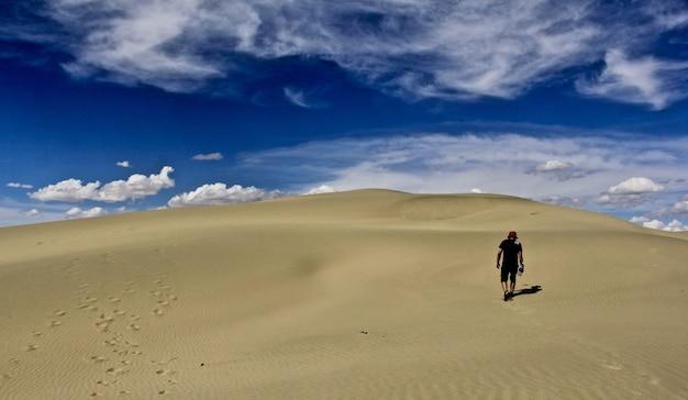 Mann, der einen roten hut in der wüste mit einem blauen himmel trägt