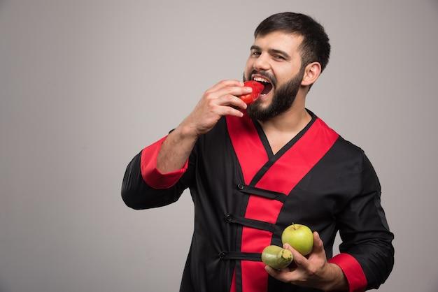 Mann, der einen roten pfeffer isst und apfel mit zucchini hält.