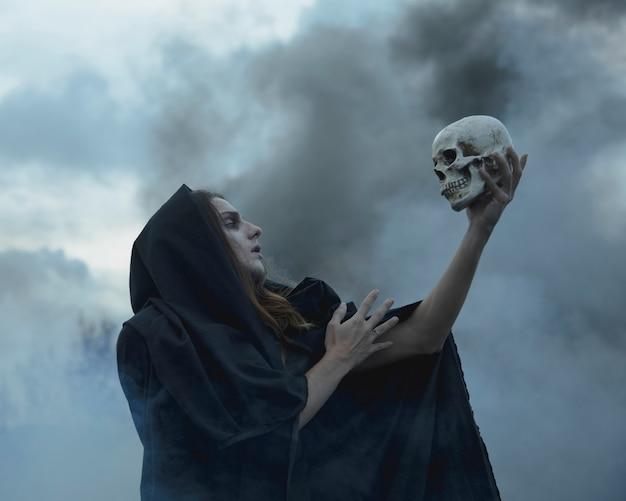 Mann, der einen schädel in der dunkelheit hält und ihn betrachtet