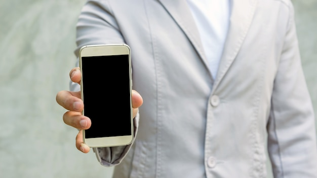 Mann, der einen smartphone auf einem grauen hintergrund hält