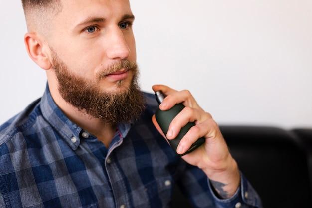 Mann, der einen spray verwendet, nachdem ein haarschnitt gehabt worden ist