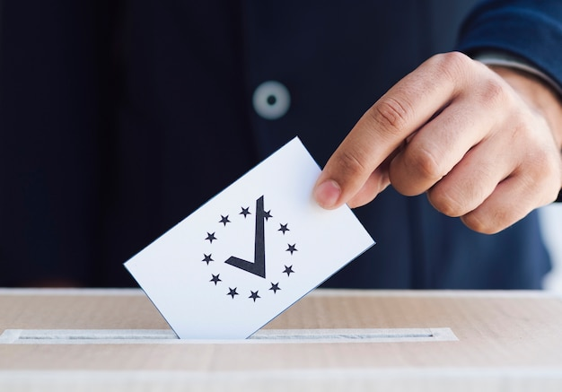 Mann, der einen stimmzettel in eine kastennahaufnahme einsetzt