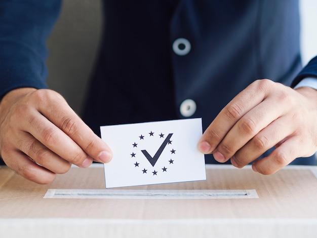 Mann, der einen stimmzettel in einen kasten einsetzt
