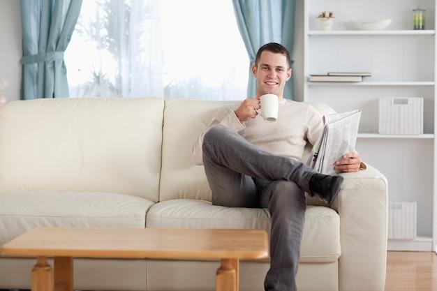 Mann, der einen tee beim lesen der nachrichten isst