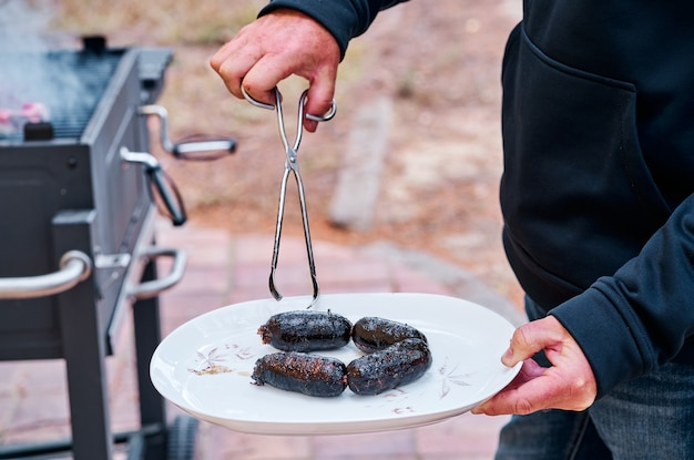 Mann, der einen teller mit einigen blutwürsten hält, die auf dem grill gekocht werden.