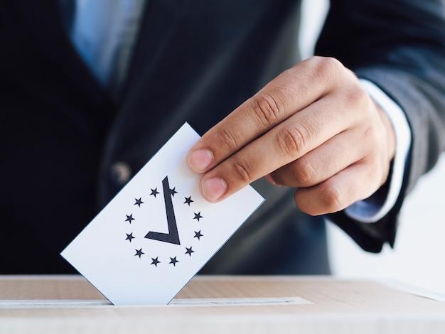 Mann, der einen überprüften stimmzettel in eine kastennahaufnahme einsetzt