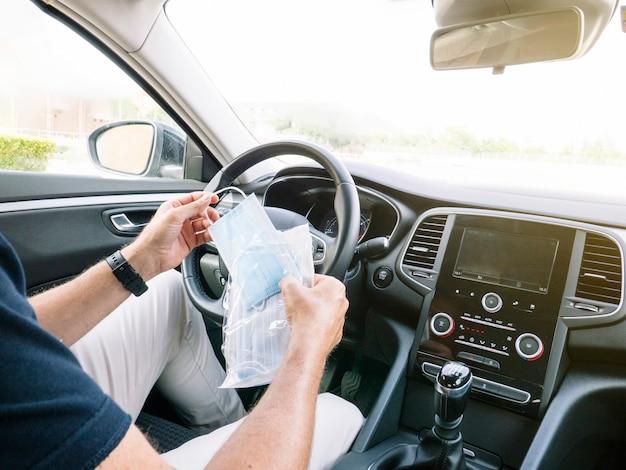 Mann, der einen umschlag mit gesichtsmasken im auto öffnet