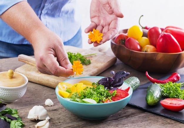 Mann, der einen vegetarischen salat kocht