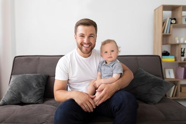Mann, der einen videoanruf mit seiner familie hat, während er sein baby hält