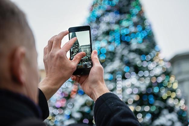 Mann, der einen weihnachtsbaum mit dem smartphone fotografiert