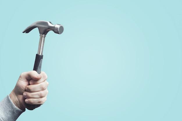 Mann, der einen weinlesehammer, werkzeug in der hand hält.