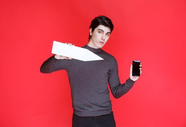 Mann, der einen weißen richtungspfeil hält, der sein smartphone zeigt