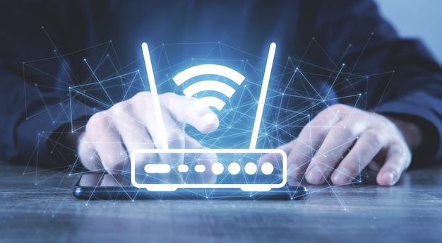 Mann, der einen wifi-router und ein netzwerk hält.