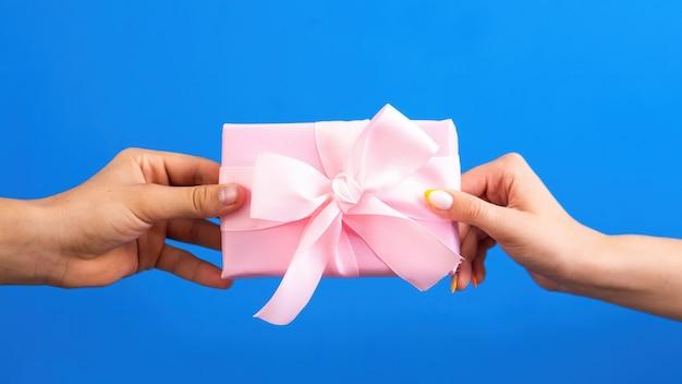 Mann, der einer frau rosa geschenkbox gibt