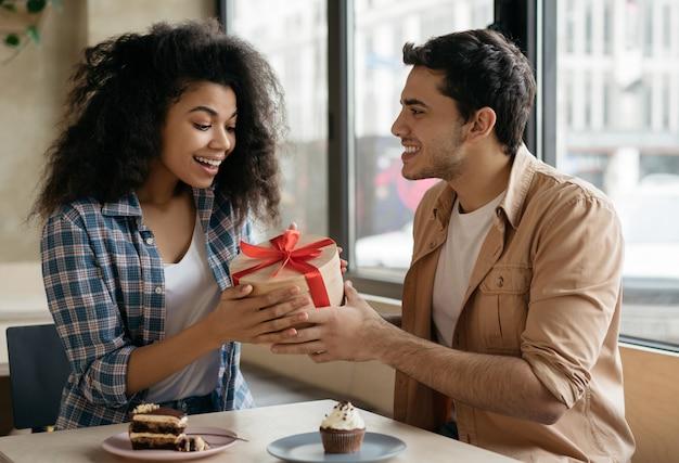 Mann, der einer schönen frau geschenkbox gibt
