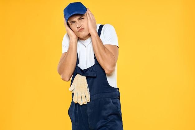 Mann, der einheitliche dienstprofis arbeitet, arbeitet gelben hintergrund