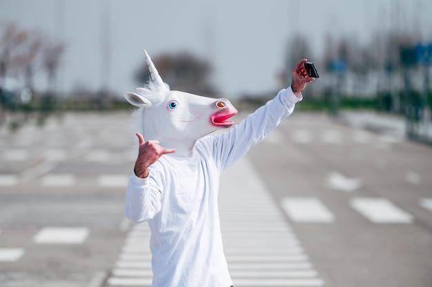 Mann, der einhornmaske trägt, die ein foto mit smartphone macht