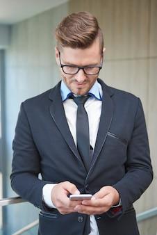 Mann, der einige wichtige dokumente am telefon überprüft
