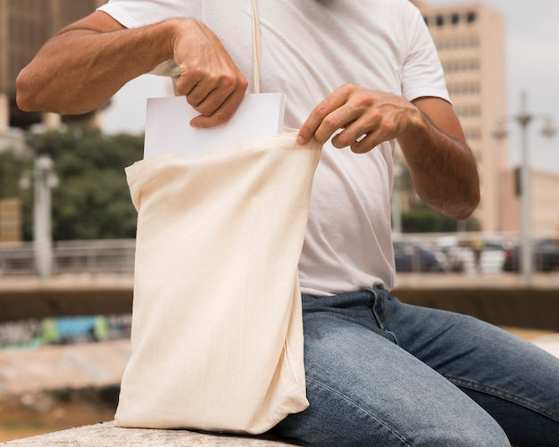 Mann, der einkaufstasche mittlerer schuss hält