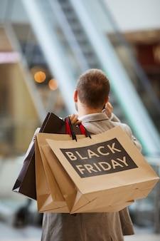 Mann, der einkaufstaschen-rückansicht hält