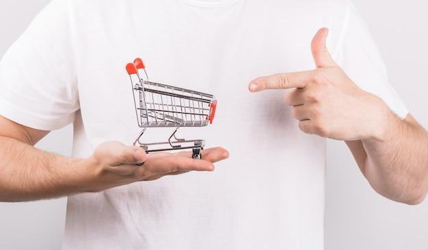 Mann, der einkaufswagen in seiner hand hält und darauf zeigt