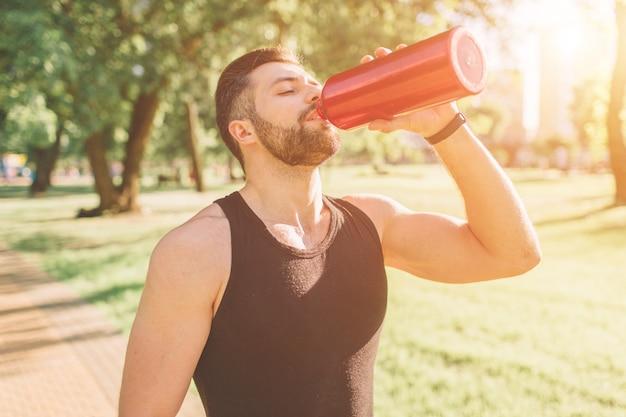 Mann, der eisenflasche und trinkwasser hält. junger hübscher gut ausgebildeter sportlicher mann, der nach draußen ausbilden stillsteht. männliches eignungsmodelltrainingstraining