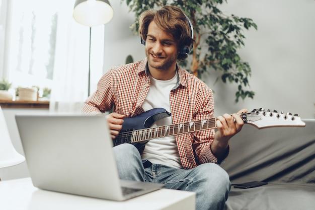 Mann, der elektrische gitarre spielt und musik in laptop aufzeichnet