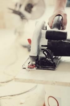 Mann, der elektrische säge an der tischlerei benutzt