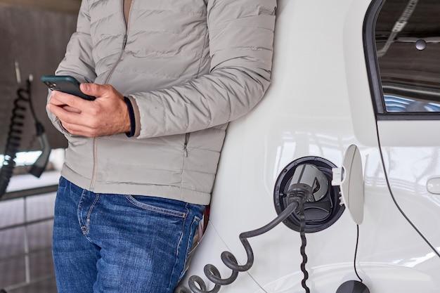 Mann, der elektrisches automobil auflädt und sein smartphone zur zahlung am ladepunkt verwendet.