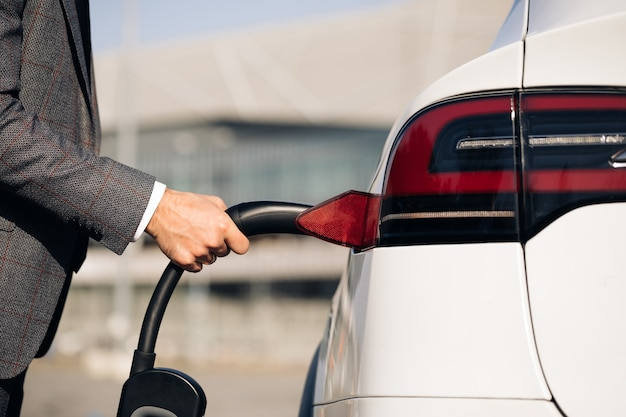 Mann, der elektroauto an der elektronischen autoladestation einsteckt