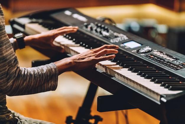 Mann, der elektronischen musikalischen tastatursynthesizer durch hände spielt.