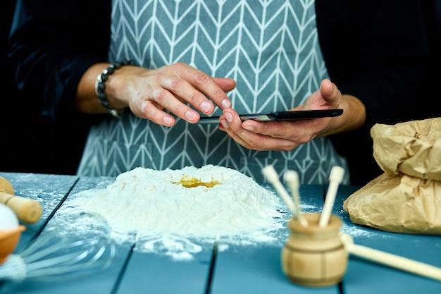 Mann, der elektronischen tablett-pc in der küche zum backen verwendet.