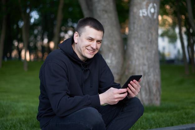 Mann, der elektronisches buch gutaussehend liest, liest e-book-tablette, das sommertag des öffentlichen parks kaukasischer mann hält, der ebook in der hand hält, die geräteschirm gekleideten schwarzen kapuzenpulli schaut