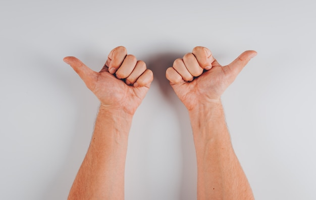 Mann, der entgegengesetzte richtungen mit seiner hände draufsicht auf weiß zeigt