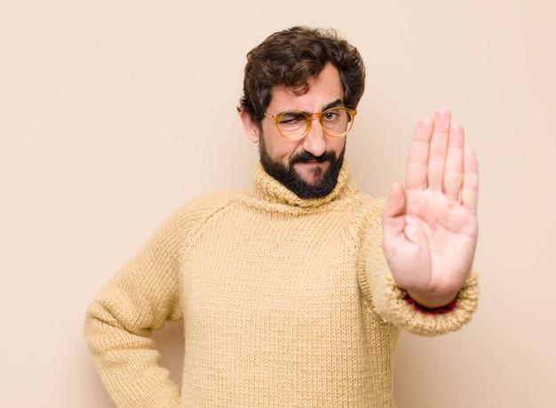 Mann, der ernst, streng, unzufrieden und wütend aussieht und offene handfläche zeigt, die stoppgeste macht
