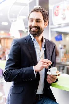 Mann, der espresso im café genießt