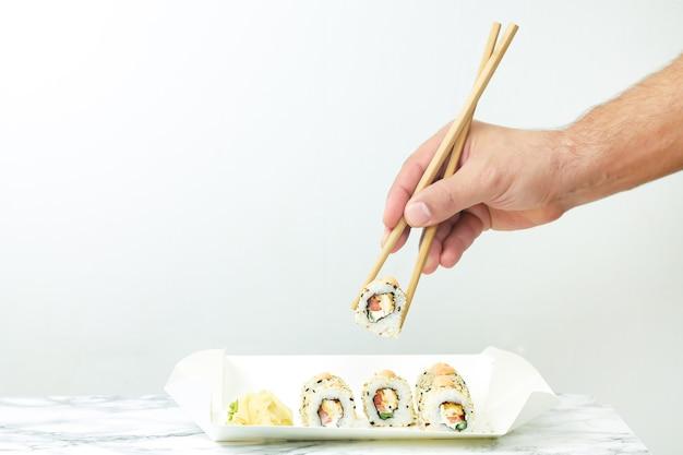 Mann, der essstäbchen hält und japanisches sushi isst, das in einwegplatte gesetzt wird.
