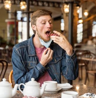 Mann, der etwas kuchen im restaurant isst