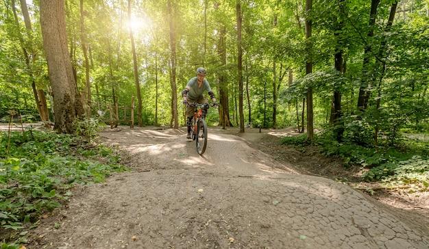 Mann, der fahrrad auf waldstraße in den schatten der hohen bäume reitet