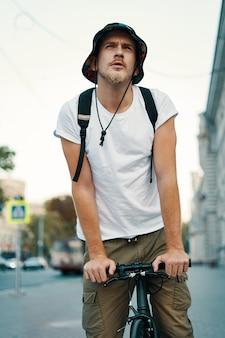 Mann, der fahrrad fährt, in neugierigen alten europäischen stadtstraßen beobachtend.